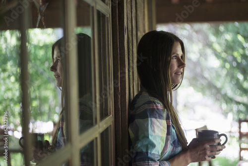Awoman with long black hair, on the porch outside a house, holding a cup of coffee.