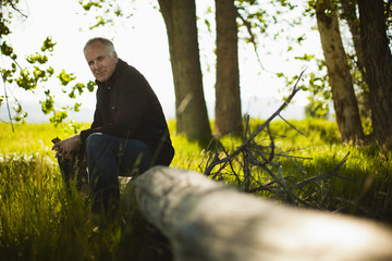 A man sitting on a fallen tree trunk in woodland.