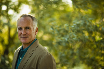 A mature man wearing a green shirt, in woodland.