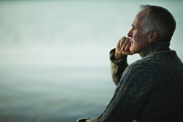 A mature man with grey hair, looking out over water, into the distance.