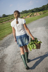 A girl in boots carrying a basket full of fresh produce.