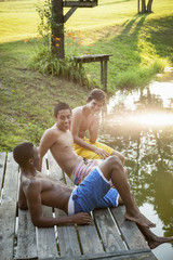 Three boys sitting on a wooden jetty, and sunlight reflecting off the water surface.