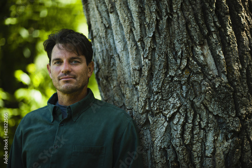 A man standing by a large tree with gnarled ridged bark.