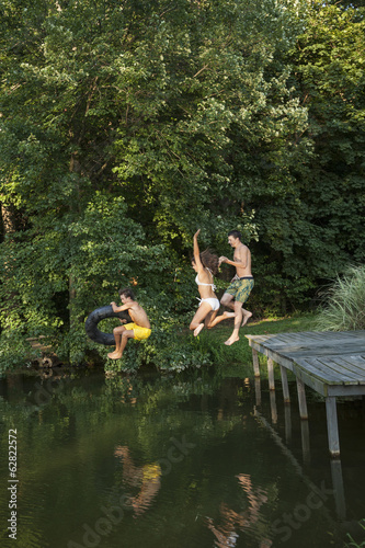 Three young boys jumping from the jetty into a still pool of water.