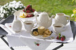 A traditional afternoon tea set out on a tea tray in a garden with white china and strawberries.
