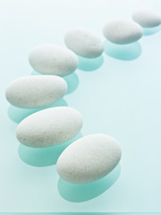 Smooth white pebbles of uniform size and colour displayed on a blue reflective glass background.