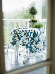 A wrought iron round table and chair on a white painted house porch, with a blue patterned tablecloth.