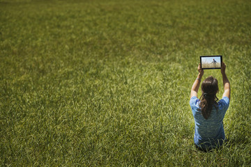 View from above of a woman sitting on grass, lifting up a personal computer notepad, looking at an image.