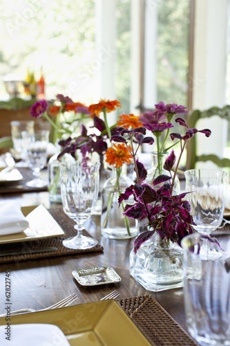 A table laid for a meal with glasses and glass vases of vivid coloured orange and maroon flower as a centrepiece.
