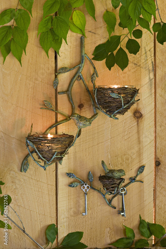 Three candle sconces on a wall, with lit tea lights, and a climbing vine.