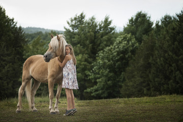 A young girl with a palomino pony in a field.