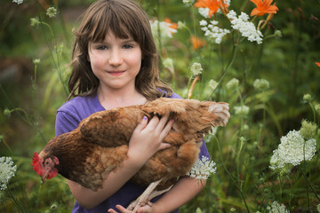 A young girl holding a domestic hen, with brown feathers and a red comb.