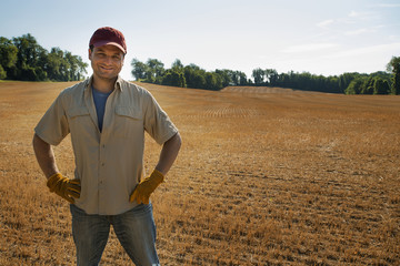 A man standing by a freshly ploughed field.