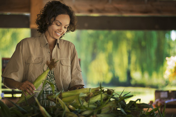 A woman with a heap of freshly picked sweet corn or maize cobs.