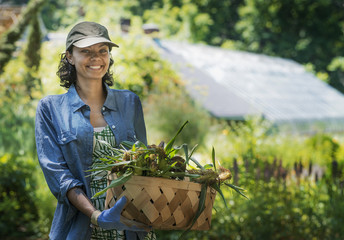 A young woman holding a large box of freshly cut vegetables.