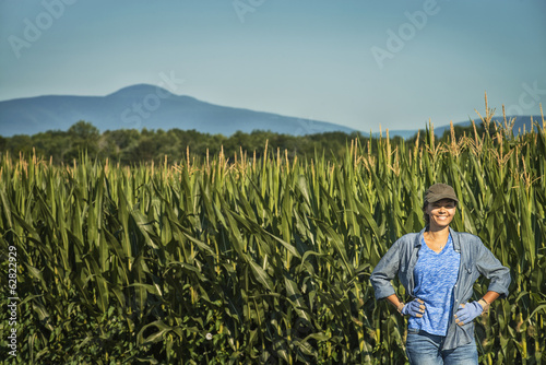 A field of tall maize plants, towering over a woman standing beside the stalks.