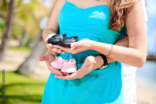 Happy pregnant woman holding baby shoes