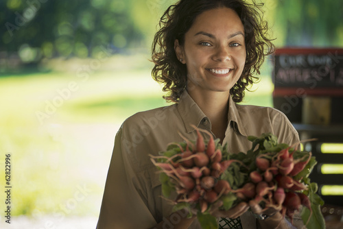 A woman carrying bunches of fresh red radishes with green leaves.