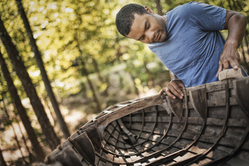 A young man repairing and sanding a traditional wooden rowing boat.