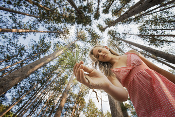 A young woman in the forest, holding a small pine sapling for planting.
