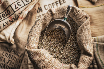 Full hessian sacks of beans and a metal scoop at a coffee bean processing shed, on a farm.