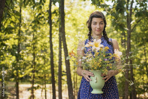 A young woman holding a vase of flowers.