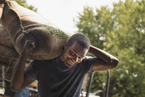 A man carrying a sack full of coffee beans at a blending and processing shed, on a farm.