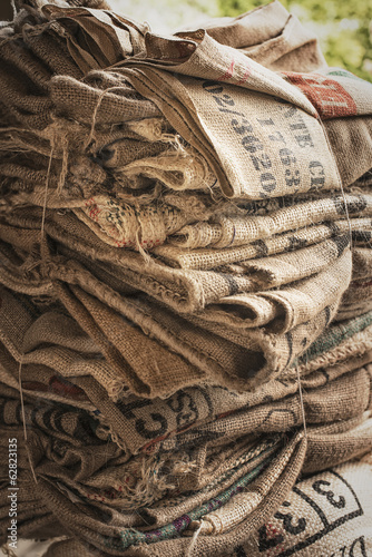 A pile of empty stamped hessian sacks bundled up for reuse or recycling, in a coffee processing plant.