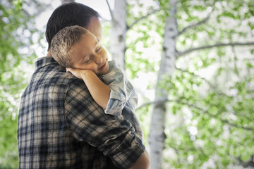 A man cradling a sleeping child, resting on his shoulder.