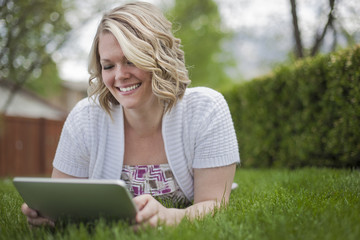 A young woman reading using a handheld electronic device, or e reader.