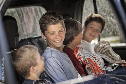 Four boys sitting in a car or truck, in a row.