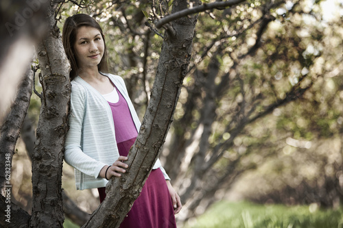 A young girl leaning against a tree in woodland.
