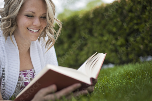 A girl sitting on the grass in a garden reading a book.