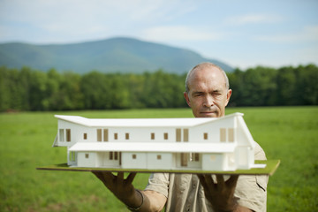 A rural scene and mountain range, and a person holding a scale model of a new building.