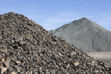 Gravel piles are used for road maintenance and construction purposes.