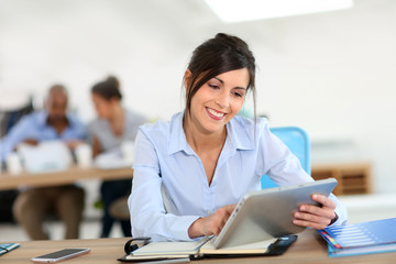 Portrait of smiling woman working with tablet