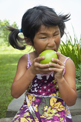 A small child with pigtails chewing a large green apple.