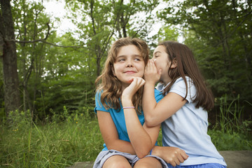 Two girls, friends sitting side by side, whispering, playing and laughing.
