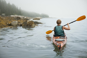 A man paddling a kayak on calm water in misty conditions. New York State, USA