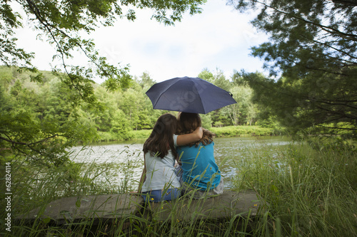 Two children, girls sitting together by a lake, under an umbrella.