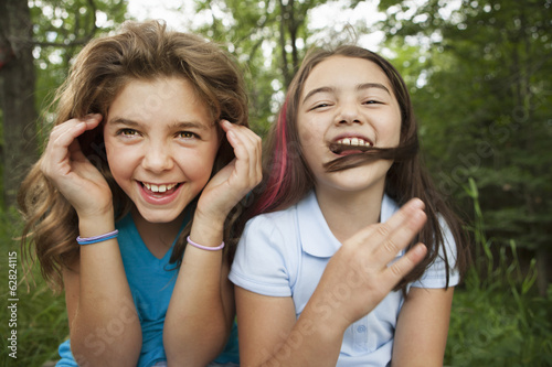 Two girls, friends sitting side by side, playing and laughing.