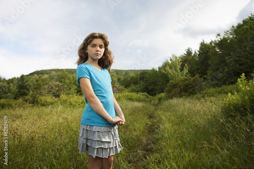 A young girl standing by a path through the long grass in a field.