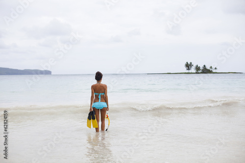 A young woman in shallow water with snorkelling gear on Samana Peninsula in the Dominican Republic.