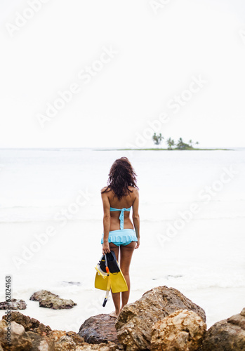 A young woman holding snorkelling gear on the Samana Peninsula in the Dominican Republic.