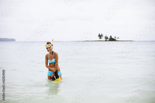 A young woman wades in shallow water on the Samana Peninsula in the Dominican Republic.
