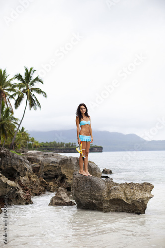 A young woman on a rock overlooking the water in Las Galeras, Samana Peninsula, Dominican Republic.