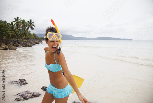 A young woman wearing a bikini on a secluded beach on the Samana Peninsula in the Dominican Republic.