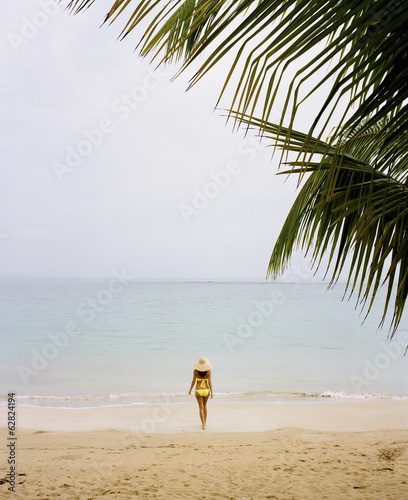 A young woman wearing a yellow bikini on a beach on the Samana Peninsula in the Dominican Republic.