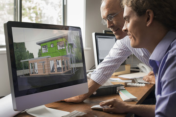 Architects discussing a green construction project, designing and building efficient environmentally friendly buildings. Green architectural practice.