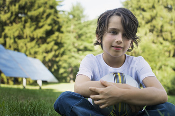 A boy holding a football, sitting on the grass. Solar panels.